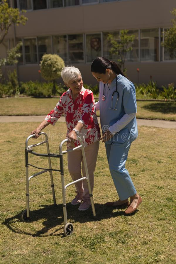 Young female doctor helping disabled senior woman in garden royalty free stock image