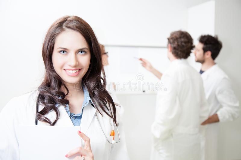 A young female doctor with her colleagues. In the doctor`s office stock photography