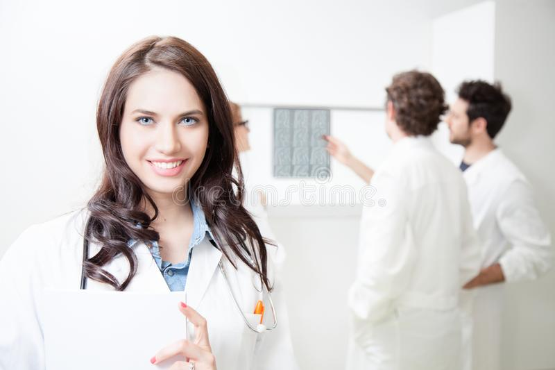 A young female doctor with her colleagues. In the doctor`s office royalty free stock image