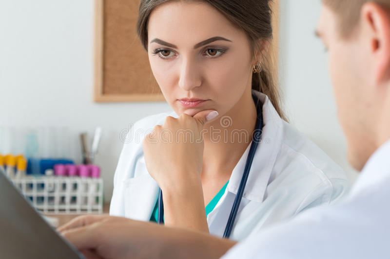 Young female doctor and her male colleague discussing x-ray image royalty free stock images
