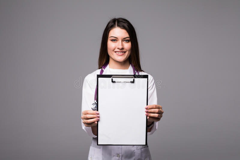 Young female doctor holding empty folder with files of desease illness. Specialist point by pen blank clipboard. Woman in medical royalty free stock photo