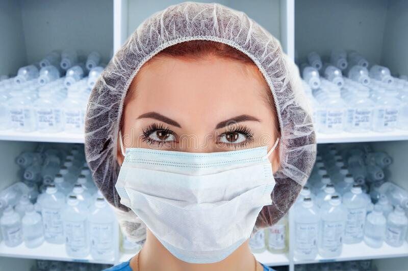 Young Female Doctor with Infusion Bottles in a Cupboard royalty free stock photo