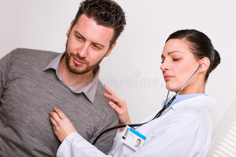 Young female doctor listening to a heartbeat stock photo