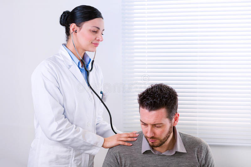 Young female doctor listening to a heartbeat stock images
