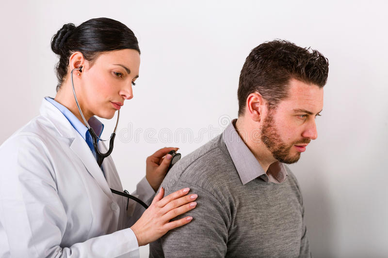 Young female doctor listening to a heartbeat royalty free stock photos