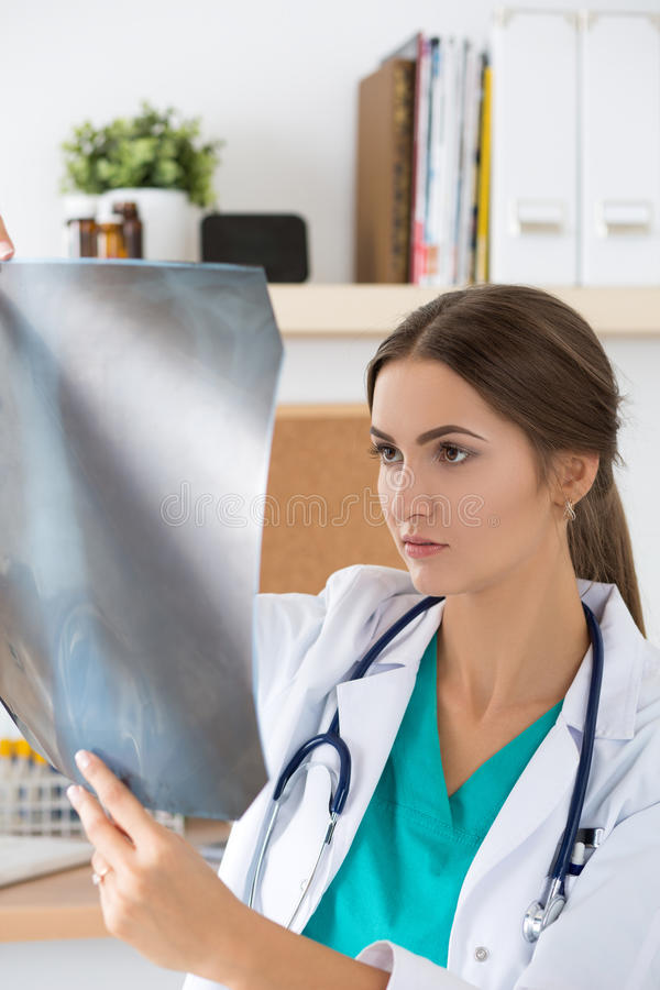 Young female doctor looking at lungs x-ray image royalty free stock images