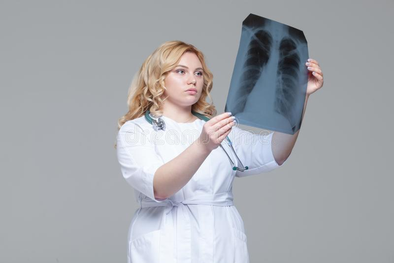 Young female doctor looking at the x-ray picture of lungs.  royalty free stock photography