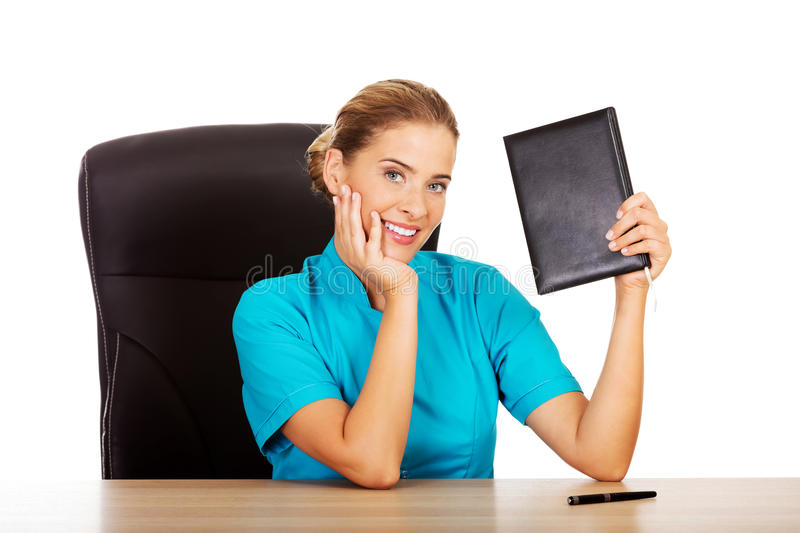 Young female doctor or nurse shows notebook royalty free stock photo
