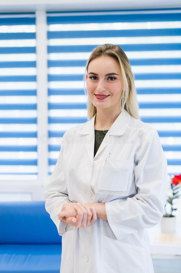Young female doctor or nurse standing at hospital reception royalty free stock image