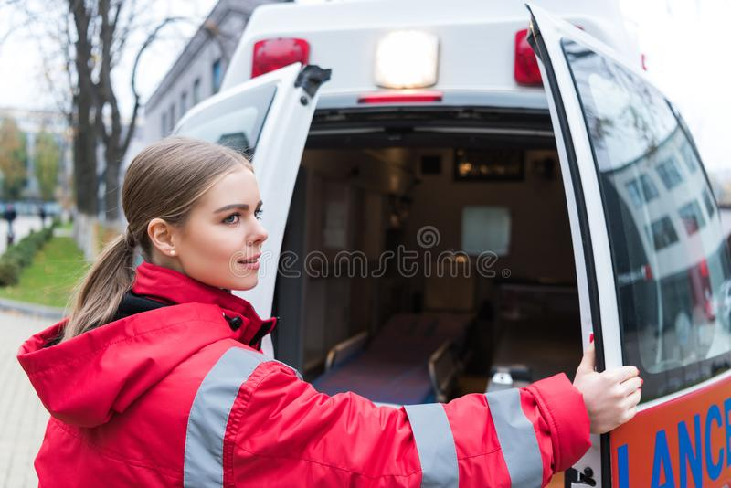Young female doctor opening ambulance doors. And looking away royalty free stock photography