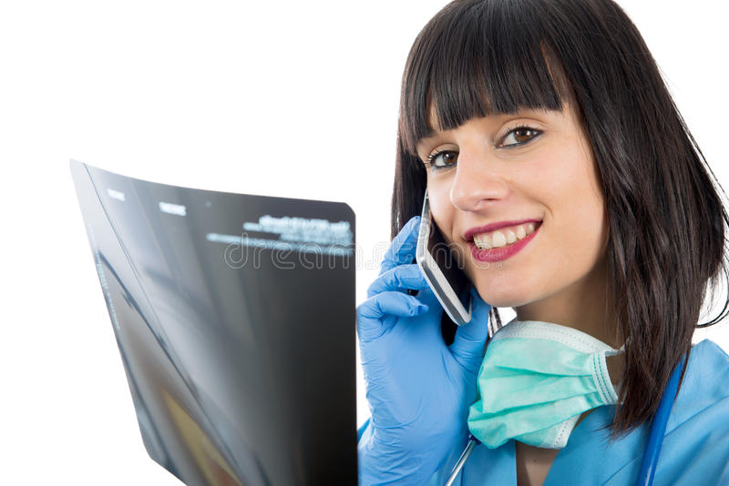 Young female doctor with phone looking at patients x-ray. A young female doctor with phone looking at patients x-ray royalty free stock photography