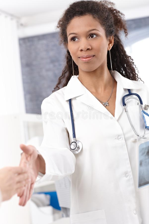 Young female doctor shaking hands royalty free stock image