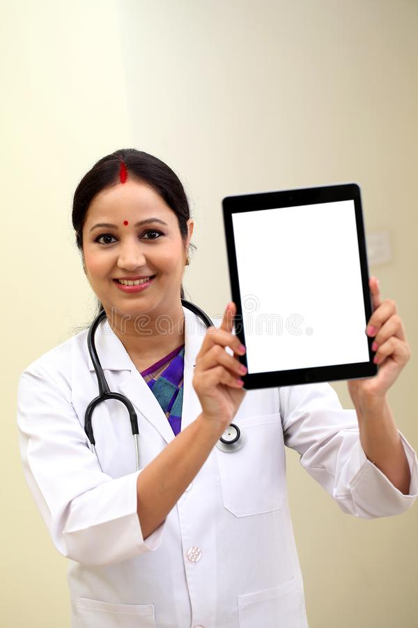 Young female doctor showing blank white screen tablet computer royalty free stock photo