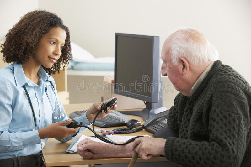 Young female Doctor taking senior man's blood pressure stock images