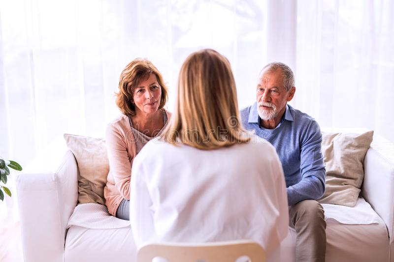 Female doctor talking to a senior couple. Young female doctor talking to a senior couple royalty free stock photo