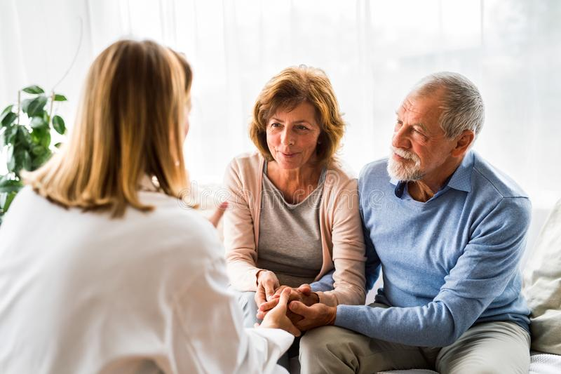 Female doctor talking to a senior couple. Young female doctor talking to a senior couple stock image