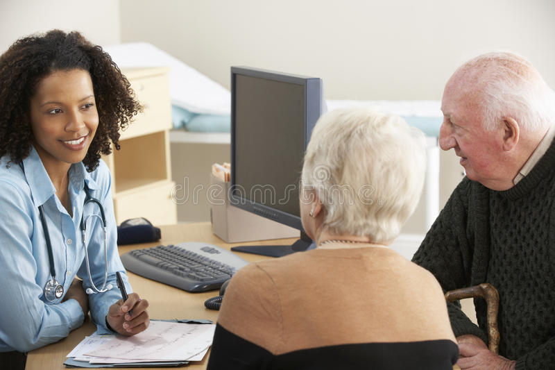 Young female Doctor talking to senior couple stock images