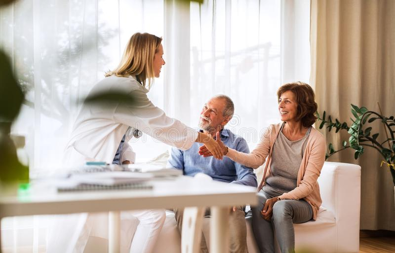 Female doctor talking to a senior couple. Young female doctor talking to a senior couple. Home visit stock images