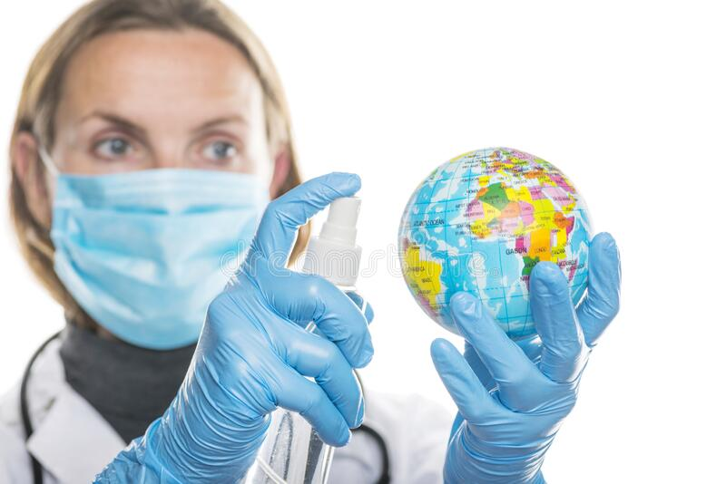 Young female doctor treats globe with an antiseptic to protect hands from coronavirus virus. Healthcare concept. COVID-19. Coronavirus pandemic stock photos
