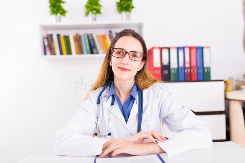 Young female doctor in uniform in doctor`s ofice writting a document royalty free stock photos