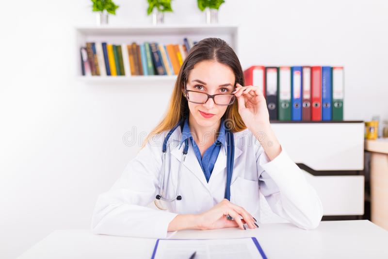 Young female doctor in uniform in doctor`s ofice writting a document stock photography