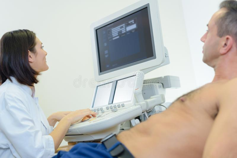 Young female doctor using ultrasound scan on male patient royalty free stock photos