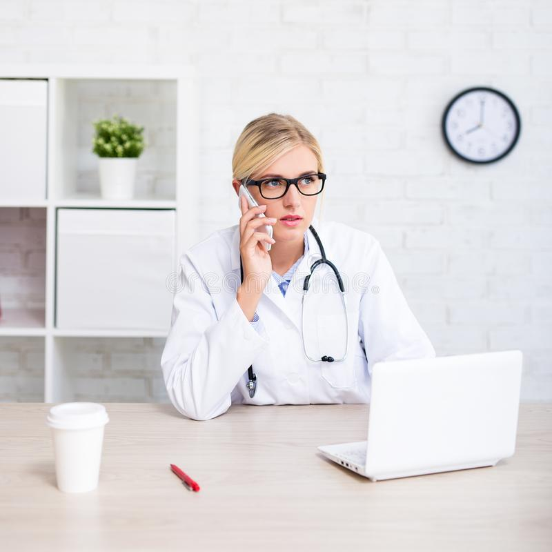 Young female doctor working with computer and talking by phone i. N modern office royalty free stock photos