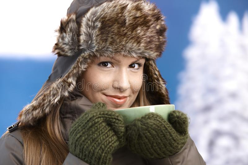 Young female dressed up warm drinking tea smiling. Young attractive female dressed up warm in coat, fur-hat and gloves, drinking hot tea, smiling royalty free stock photography