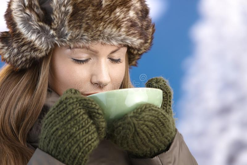 Young female dressed up warm enjoying hot tea. Young attractive female dressed up warm in coat, fur-hat and gloves, drinking hot tea, eyes closed stock photo