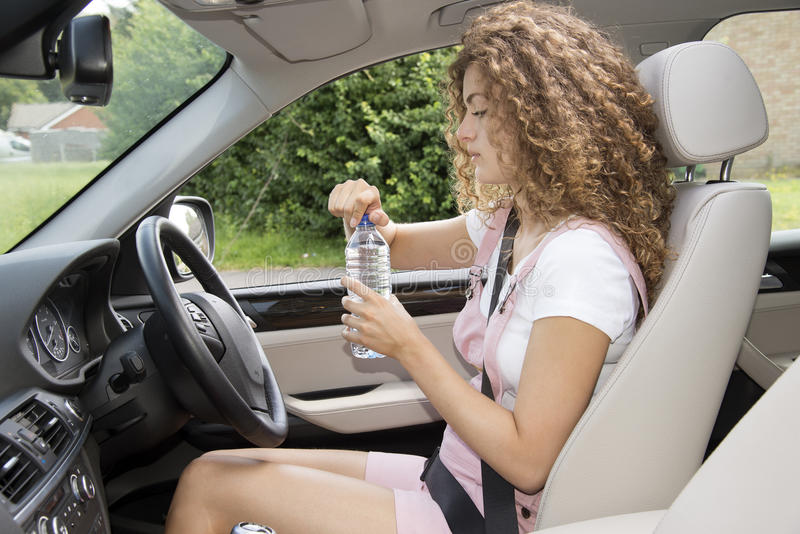 Young female driver drinking from a bottle of water royalty free stock image
