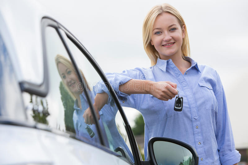 Young Female Driver Holding Car Keys Next To Vehicle stock photo