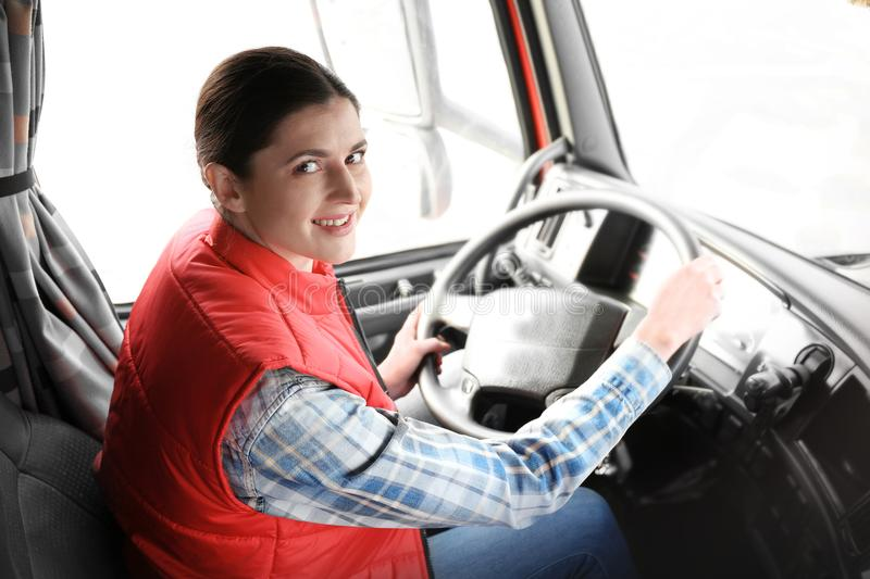 Young female driver sitting in cabin of big truck. Young female driver sitting in cabin of big modern truck stock photo