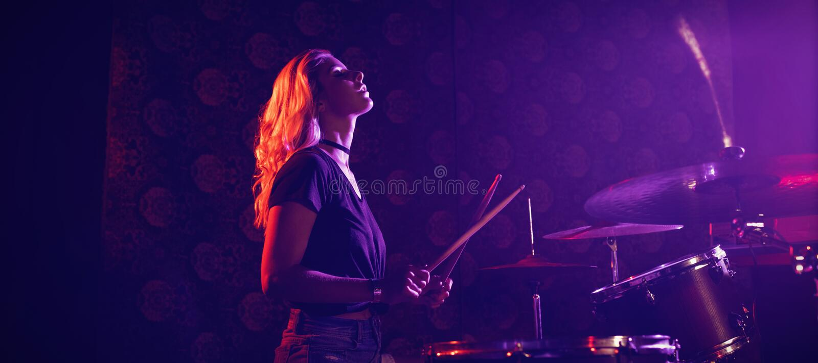 Young female drummer performing in illuminated nightclub royalty free stock photography