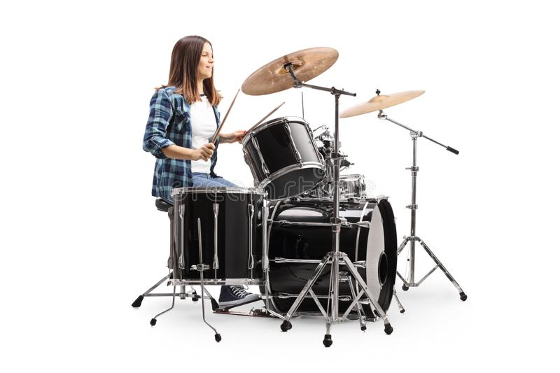 Young female drummer playing a drum set stock photography