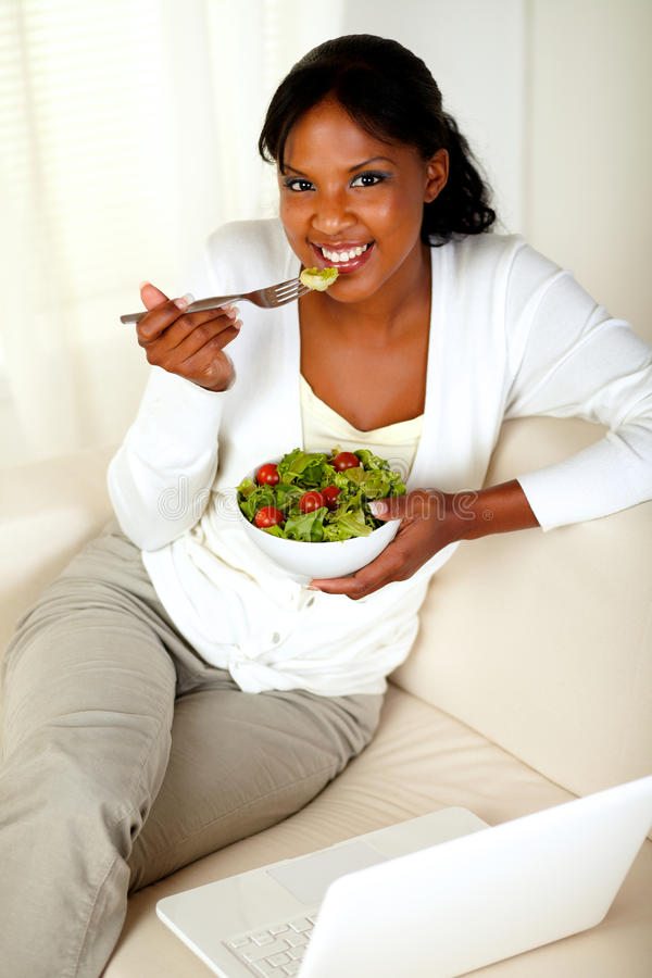 Young female eating healthy salad looking at you royalty free stock photography