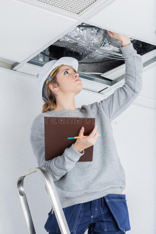 Young female electrician installing electric device in ceiling royalty free stock image