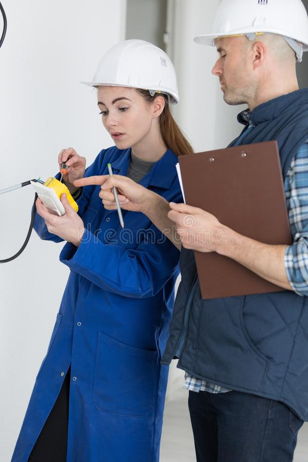 Young female electrician installing electrical socket on wall with screwdriver. Voltage stock photos