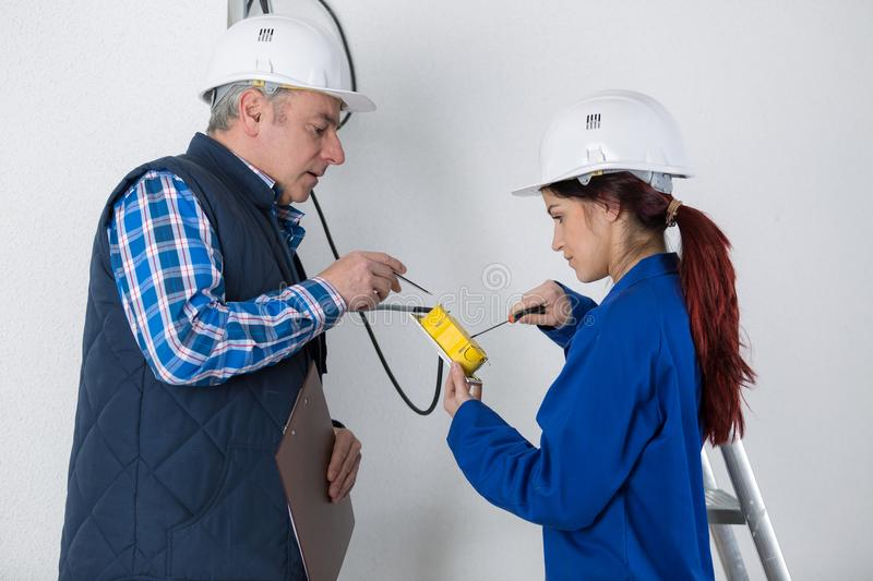 Young female electrician with mentor. Female stock images