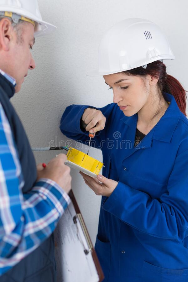 Young female electrician with teacher stock photography