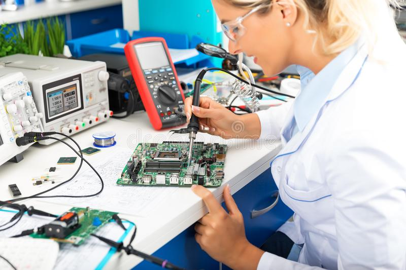 Young female electronic engineer soldering computer motherboard royalty free stock photos