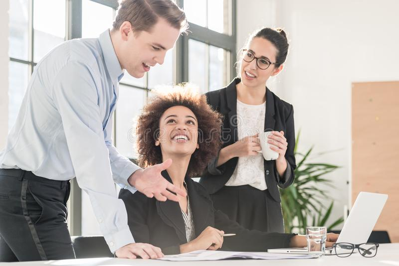 Young female employee asking for advice her experienced colleagu stock photography