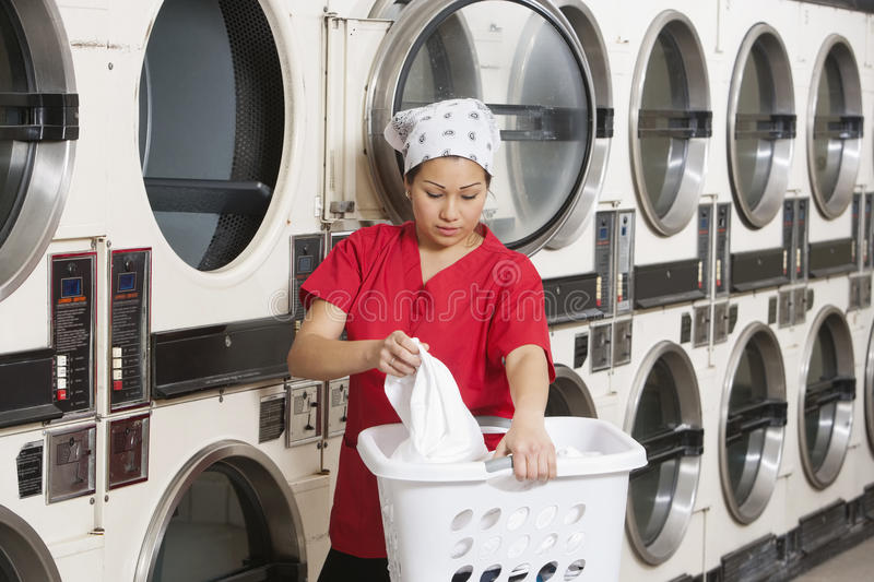 Young female employee carrying laundry basket with washing machines in background stock photo
