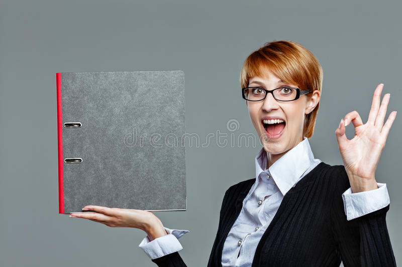 Young Female Employee Gesturing Perfect Job And Holding Folder Stock Photos