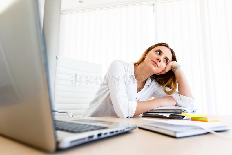 Young female employee gets bored at workplace royalty free stock images