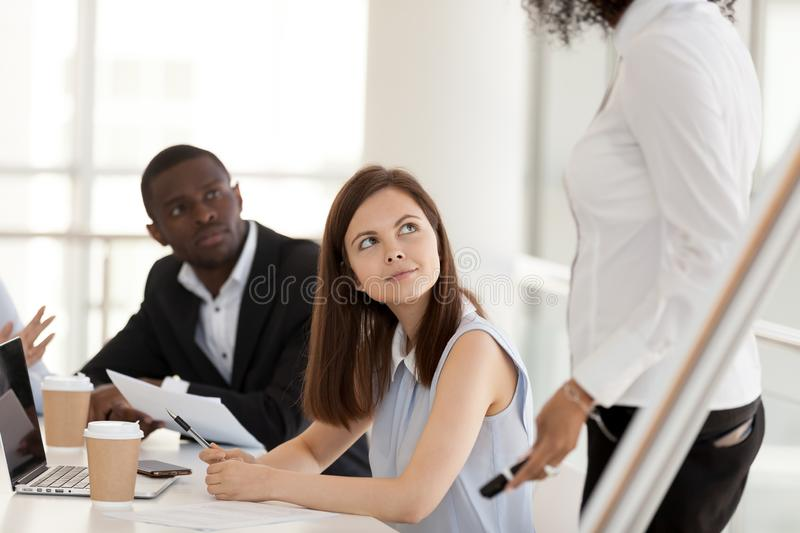 Young female employee looking at business coach at company meeting royalty free stock images