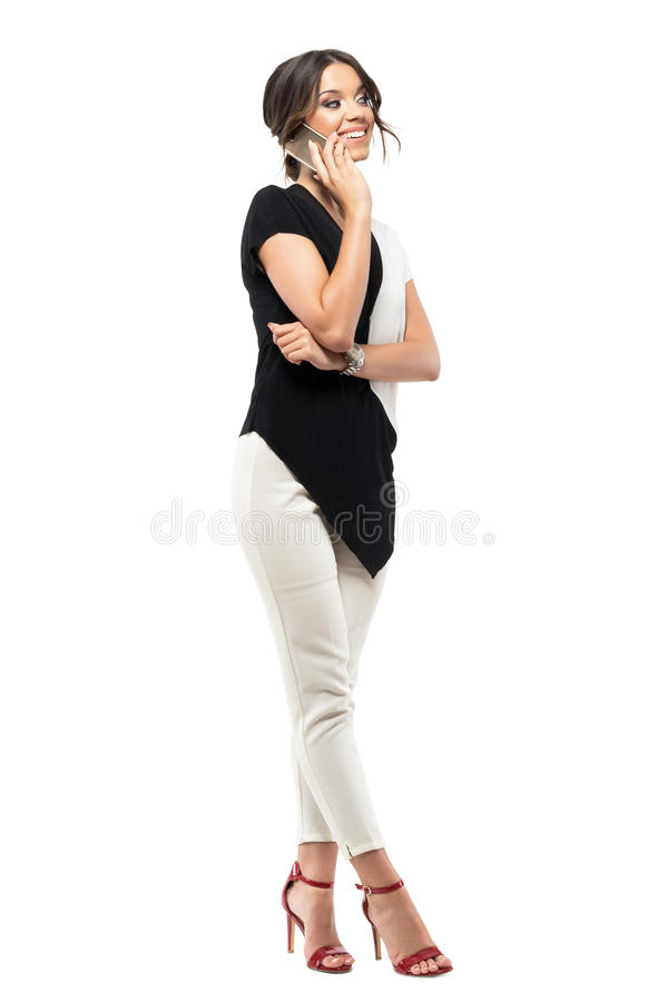 Young female employee relaxing on pause smiling and talking on the mobile phone. Full body length portrait isolated on white studio background royalty free stock photography