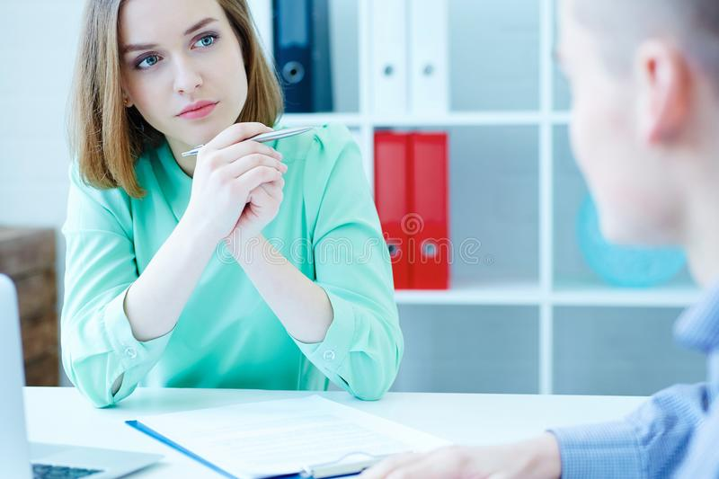 Young female employee of the staffing agency listening attentively the male job seeker. Business, office, law and legal royalty free stock image