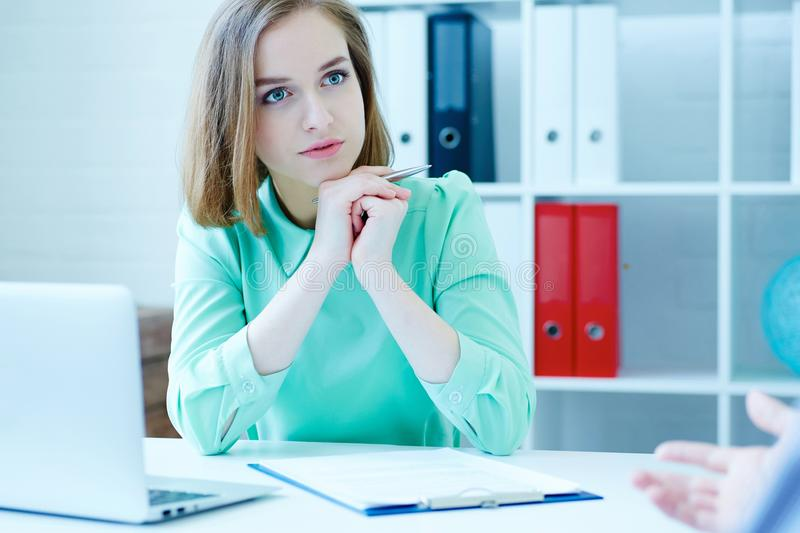 Young female employee of the staffing agency listening attentively the male job seeker. Business, office, law and legal concept stock images