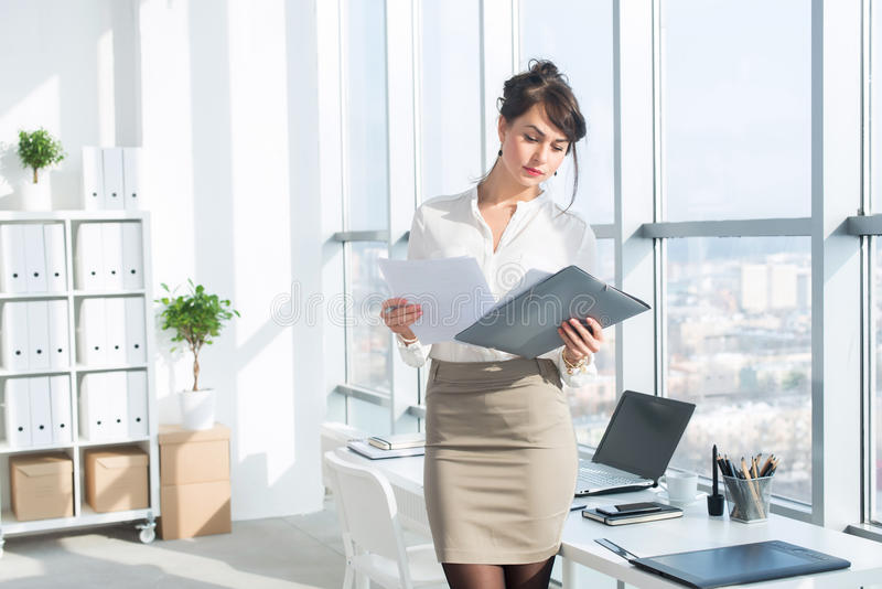 Young female employee, standing in office, wearing her work suit, reading business papers attentively, front view. Portrait stock image