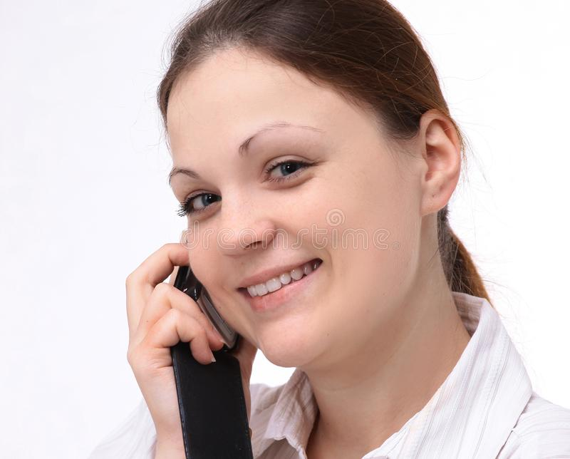 Young female employee talking on a cell phone. isolated on white. royalty free stock photography